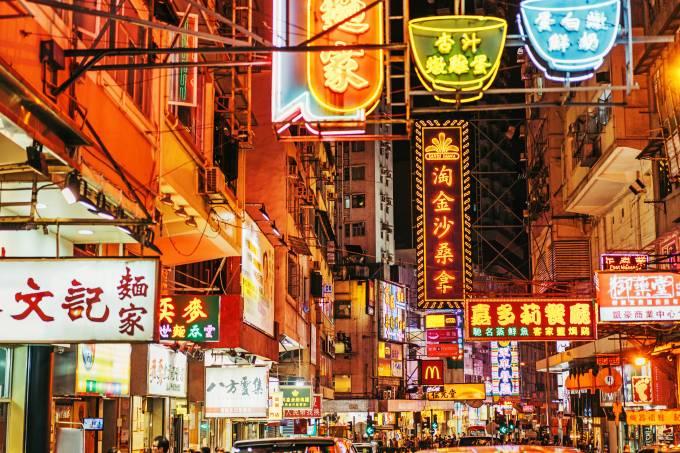 Rua comercial Kowloon, Hong Kong, na Ásia, com lojas e placas em neon