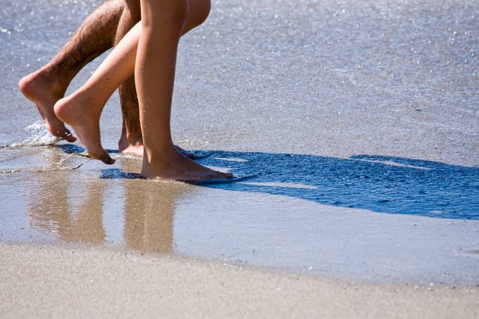 Casal caminha pela praia