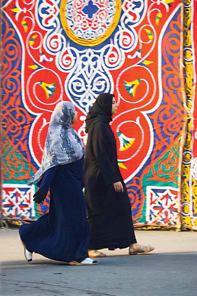 Mulheres de roupas escuras andando em frente de arabescos coloridos