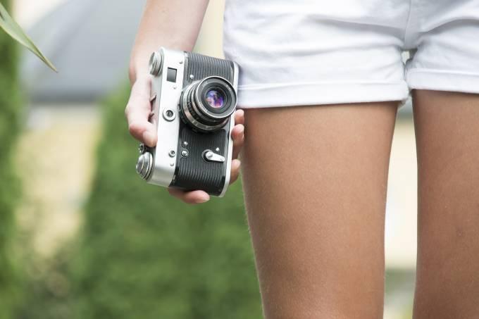 Mulher segura câmera fotográfica analógica na mão com pernas e short branco ao fundo