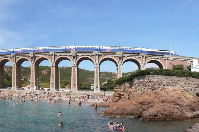 Trem passa por cima de ponte dos arcos em praia de Côte D' Azur, no sul da França