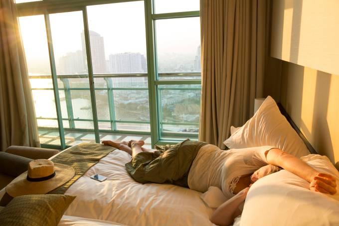 Mulher tenta dormir em quarto de hotel em Bangcoc, na Tailandia, durante o dia por jet lag