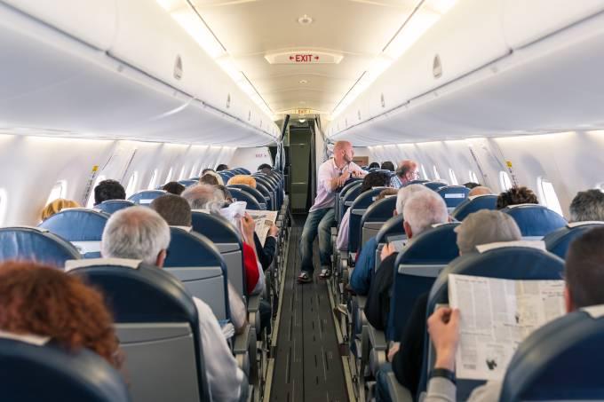 Cabine de um voo comercial de avião da Air France com passageiros a bordo lendo jornal