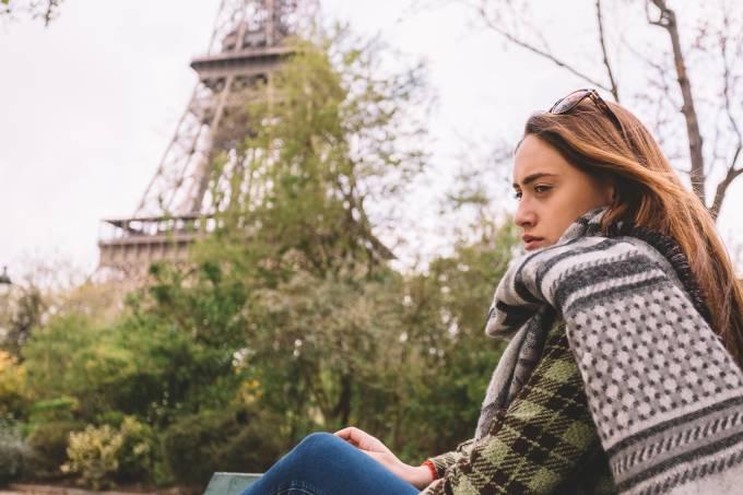 Mulher francesa triste em frente a Torre Eiffel em Paris