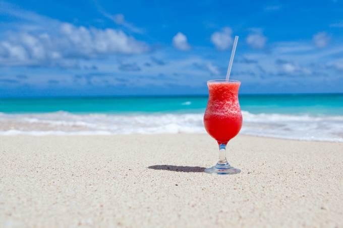 Drink de batida de frutas na areia da praia na beira do mar