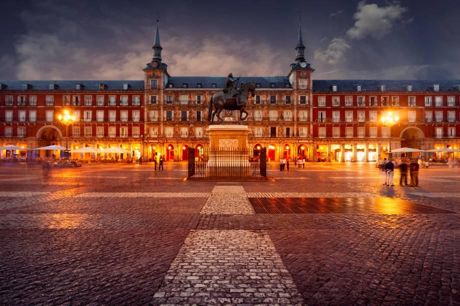 """<strong>Plaza Mayor – <a href=""""https://viagemeturismo.abril.com.br/cidades/madri/"""" target=""""_blank"""" rel=""""noopener"""">Madri</a> – <a href=""""https://viagemeturismo.abril.com.br/paises/espanha/"""" target=""""_blank"""" rel=""""noopener"""">Espanha</a></strong> Boa parte das cidades espanholas e mesmo aquelas fundadas e conquistadas por eles nas Américas têm sua <strong>Plaza Mayor</strong>. Centro gravitacional da vida cívica, mercado e sede de edifícios governamentais, tudo girava ao seu redor. A mais bela e definitiva dessas praças não poderia estar em outro lugar, senão na capital do país. Ao longo de sua história, a Plaza Mayor de Madri foi palco de touradas, execuções e autos de fé da radical Inquisição espanhola, um local onde igreja e coroa atestavam seu poder perante o povo. O formato retangular e a relativa simetria no desenho dos edifícios é obra de sucessivos monarcas, mas boa parte das atuais características se devem a Filipe III, cuja estátua está fixada no centro da praça. Cafés e restaurantes espalham sob as arcadas centenas de mesas durante o dia, um ótimo lugar para ver a vida passar<em>Busque hospedagem em Madri</em>"""
