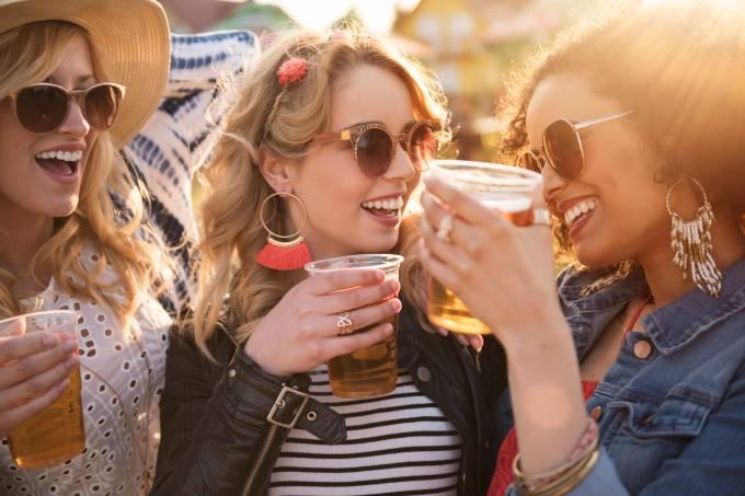 Mulheres brindam com copos de cerveja FOTO gpointstudio iStock-538879148