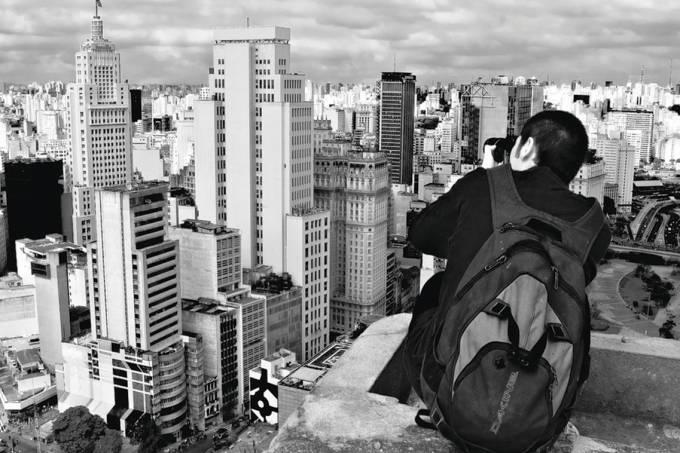 Homem fotografa o centro da cidade de São Paulo do alto de um prédio