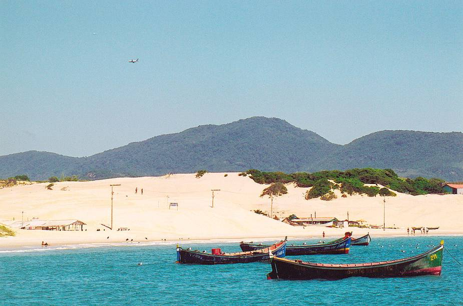 """As praias mais selvagens e sossegadas ficam no sul da ilha. São tantas praias que nem todas têm nome. Como se não as bastasse, Floripa também agrada com suas lagoas, dunas, montanhas e mangues. <a href=""""https://www.booking.com/searchresults.pt-br.html?aid=332455&lang=pt-br&sid=eedbe6de09e709d664615ac6f1b39a5d&sb=1&src=searchresults&src_elem=sb&error_url=https%3A%2F%2Fwww.booking.com%2Fsearchresults.pt-br.html%3Faid%3D332455%3Bsid%3Deedbe6de09e709d664615ac6f1b39a5d%3Bcity%3D-633693%3Bclass_interval%3D1%3Bdest_id%3D-634523%3Bdest_type%3Dcity%3Bdtdisc%3D0%3Bfrom_sf%3D1%3Bgroup_adults%3D2%3Bgroup_children%3D0%3Binac%3D0%3Bindex_postcard%3D0%3Blabel_click%3Dundef%3Bno_rooms%3D1%3Boffset%3D0%3Bpostcard%3D0%3Braw_dest_type%3Dcity%3Broom1%3DA%252CA%3Bsb_price_type%3Dtotal%3Bsearch_selected%3D1%3Bsrc%3Dsearchresults%3Bsrc_elem%3Dsb%3Bss%3DCanela%252C%2520%25E2%2580%258BRio%2520Grande%2520do%2520Sul%252C%2520%25E2%2580%258BBrasil%3Bss_all%3D0%3Bss_raw%3DCanela%3Bssb%3Dempty%3Bsshis%3D0%3Bssne_untouched%3DCambar%25C3%25A1%26%3B&ss=Florian%C3%B3polis%2C+%E2%80%8BSanta+Catarina%2C+%E2%80%8BBrasil&ssne=Canela&ssne_untouched=Canela&city=-634523&checkin_monthday=&checkin_month=&checkin_year=&checkout_monthday=&checkout_month=&checkout_year=&no_rooms=1&group_adults=2&group_children=0&highlighted_hotels=&from_sf=1&ss_raw=Florian%C3%B3polis&ac_position=0&ac_langcode=xb&dest_id=-643337&dest_type=city&search_pageview_id=91cd738843c90212&search_selected=true&search_pageview_id=91cd738843c90212&ac_suggestion_list_length=5&ac_suggestion_theme_list_length=0"""" target=""""_blank"""" rel=""""noopener""""><em>Busque hospedagens em Florianópolis</em></a>"""
