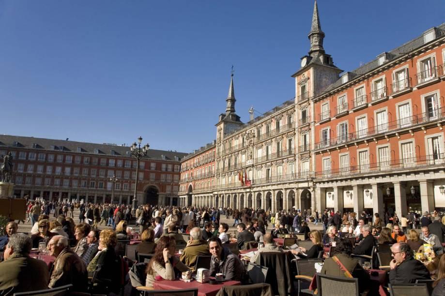 Sob as arcadas da Plaza Mayor de Madri, do século 17, espalham-se mesinhas de diversos bares e cafés