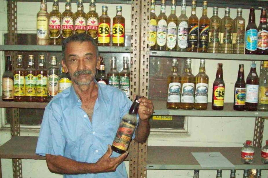 """O acervo do <a href=""""http://viajeaqui.abril.com.br/estabelecimentos/br-pe-tracunhaem-atracao-museu-da-cachaca"""" target=""""_blank"""">Museu da Cachaça</a> com cerca de 12.400 rótulos de cachaça é a principal atração de Tracunhaém. Há pontos de venda e degustação dentro do museu e a caninha maioral da casa é a primeira cachaça industrializada do Brasil (1756 Engenho Monjope, de Igarassu, PE). Na foto: José Moura, proprietário do local, e parte do acervo."""
