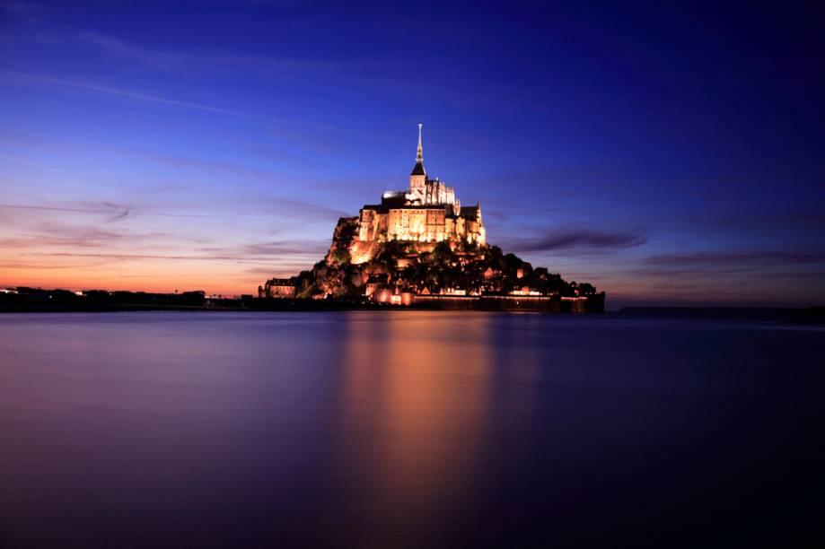 À noite, as luzes acesas no castelo gótico e na muralha do Monte Saint-Michel, na Costa da Normandia, causam um estado de quase hipnose