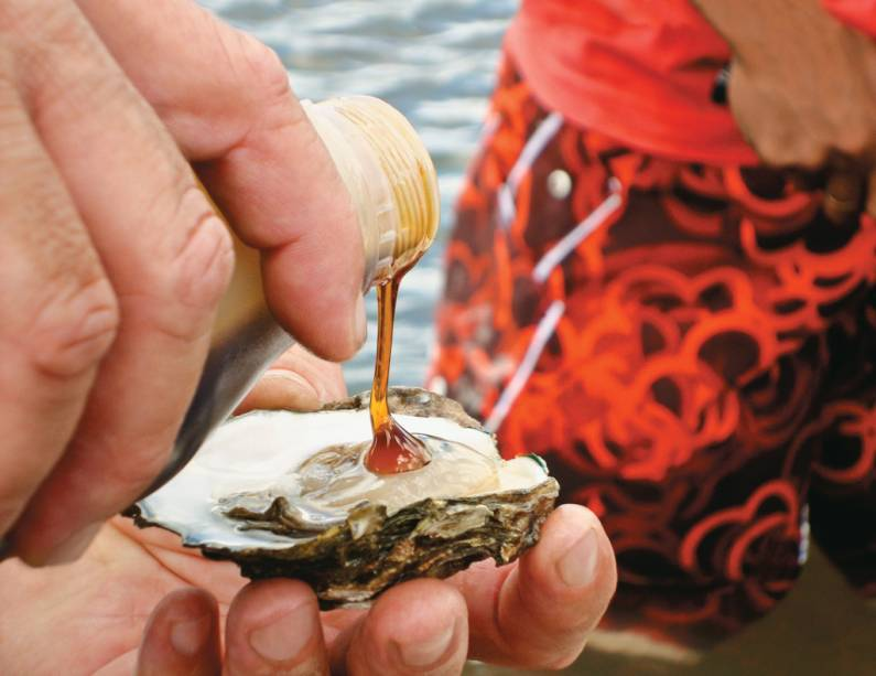 """Ostra servida com azeite e mel durante passeio ao criadouro de ostras da Vila Palateia, conhecida como """"paraíso das ostras"""""""