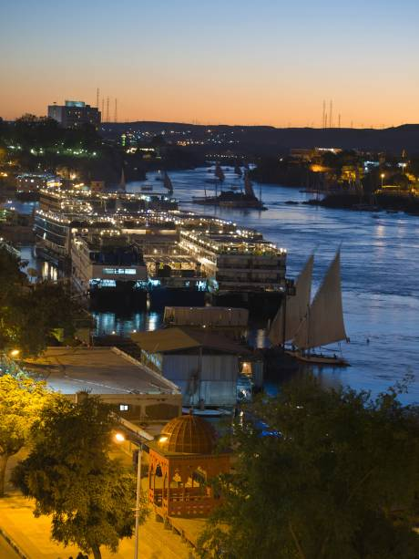 Pôr-do-sol em Aswan, com feluccas e dahabiyas, embarcações de cruzeiro, ancoradas ao longo do rio Nilo