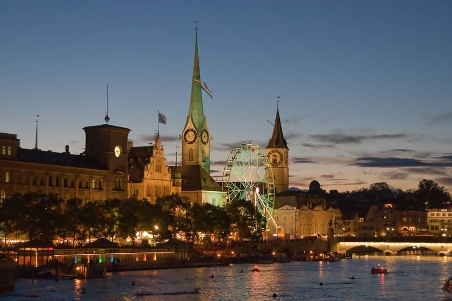 Vista noturna das igrejas Fraumünster e St. Peterskirche, a partir do rio Limmat, em Zurique