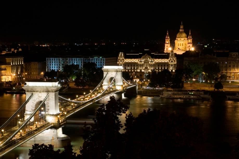 A ponte suspensa Szechenyi é uma das principais ligações entre Buda e Peste. Batizada em nome do estadista István Szécheny, foi a primeira ligação permanente na capital húngara e à época de sua inauguração era uma das mais longas do mundo. Ao fundo, com sua cúpula iluminada, encontra-se a Catedral de Santo Estevão