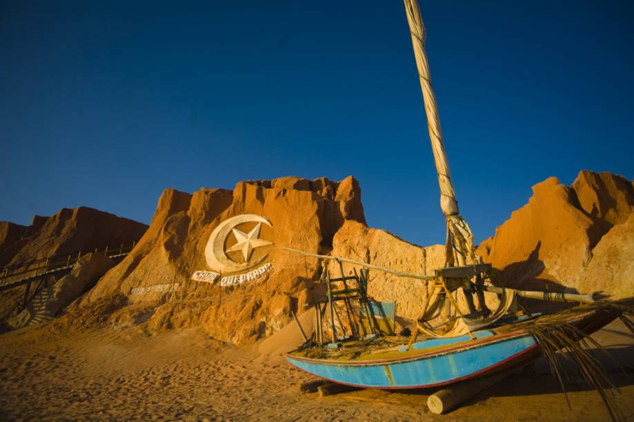 Lua e estrela esculpidas na parede de areia são o símbolo de Canoa Quebrada