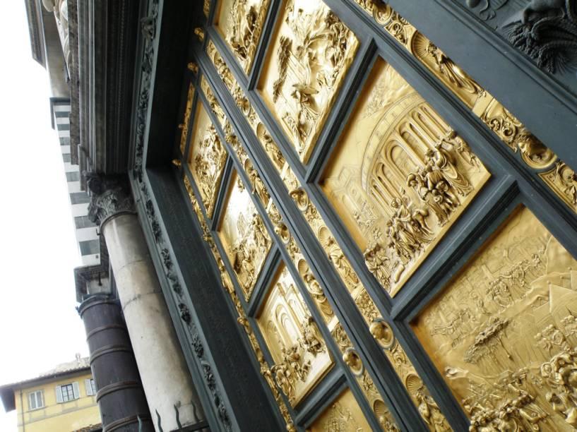 """As portas do <a href=""""https://www.museumflorence.com/monuments/3-baptistry"""" target=""""_blank"""" rel=""""noopener""""><strong>batistério</strong></a> da <strong>Catedral de Florença</strong> são decoradas com cenas da Bíblia. A porta leste foi chamada de """"portão do paraíso"""" por Michelangelo."""