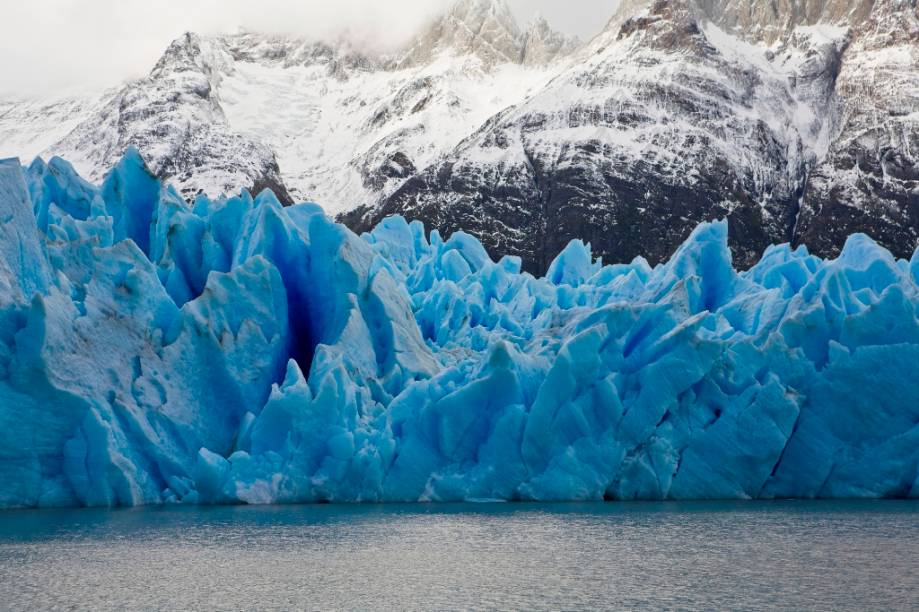 """A <strong><a href=""""http://viajeaqui.abril.com.br/cidades/chile-torres-del-paine"""" rel=""""geleira Grey"""" target=""""_blank"""">Geleira Grey</a></strong>, de cerca de 30 quilômetros de comprimento, é parte do campo de gelo patagônico sul, uma das maiores concentrações glaciais fora dos pólos terrestres. Vista do céu, a formação parece um enorme urso branco avançando sobre uma massa de água. No entanto, a geleira está em franco processo de retrocesso, desprendendo gigantescos blocos azulados sobre as águas do Lago Grey"""
