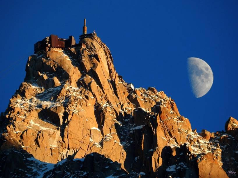 """O topo do Mont Blanc, com a Lua ao fundo; o monte mais alto dos <a href=""""http://viajeaqui.abril.com.br/materias/esqui-e-vida-selvagem-na-francesa-chamonix"""" rel=""""Alpes Franceses"""" target=""""_blank"""">Alpes Franceses</a> fica em <a href=""""http://viajeaqui.abril.com.br/materias/esqui-e-vida-selvagem-na-francesa-chamonix"""" rel=""""Chamonix"""" target=""""_blank"""">Chamonix</a>, um dos destinos de esqui na região mais frequentados por brasileiros"""
