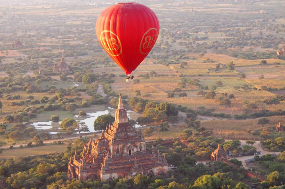 """Uma das maneiras terrestres de conhecer os milhares templos budistas espalhados em <a href=""""http://viagemeturismo.abril.com.br/cidades/bagan-4/"""">Bagan</a>, esse platô à beira do rio Ayeyarwady, em <a href=""""http://viagemeturismo.abril.com.br/paises/mianmar/"""">Mianmar</a>, é em carroças. Para ter uma visão mais do que privilegiada das ruínas, vale a pena se aventurar em um passeio de balão. Você pode agendar o seu passeio através do <a href=""""http://www.go-myanmar.com/booking?edit[field_booking_type][und][0][field_balloon_location][und]=92#balloons"""" target=""""_blank"""">site oficial de turismo de Mianmar</a>."""