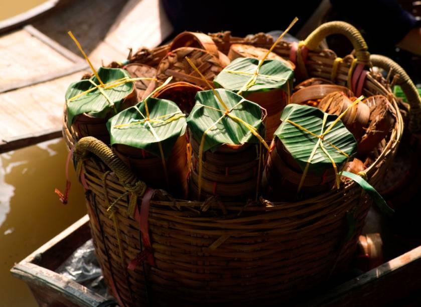 Abaixo o plástico! Vendedores de comida no mercado flutuante de Damnoen Saduak envolvem seus preparos em caixinhas de bambu, embalados em folhas de bananeira: bonito, sustentável e funcional