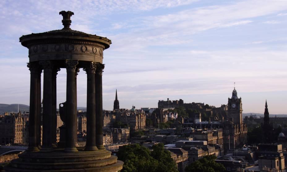 "Monumento a Dugald Stewart e, ao fundo, o Castelo de <a href=""http://viajeaqui.abril.com.br/cidades/escocia-edimburgo"" rel=""Edimburgo"" target=""_blank"">Edimburgo</a>"