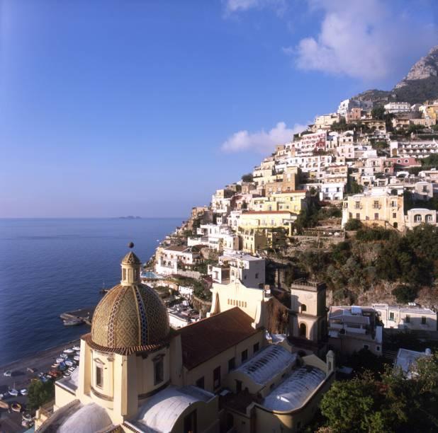 """Vista da orla do vilarejo de <a href=""""http://viajeaqui.abril.com.br/cidades/italia-positano"""" rel=""""Positano"""">Positano</a>, na Costa Amalfitana, com a cúpula de cerâmica da Igreja Santa Maria Assunta em primeiro plano"""