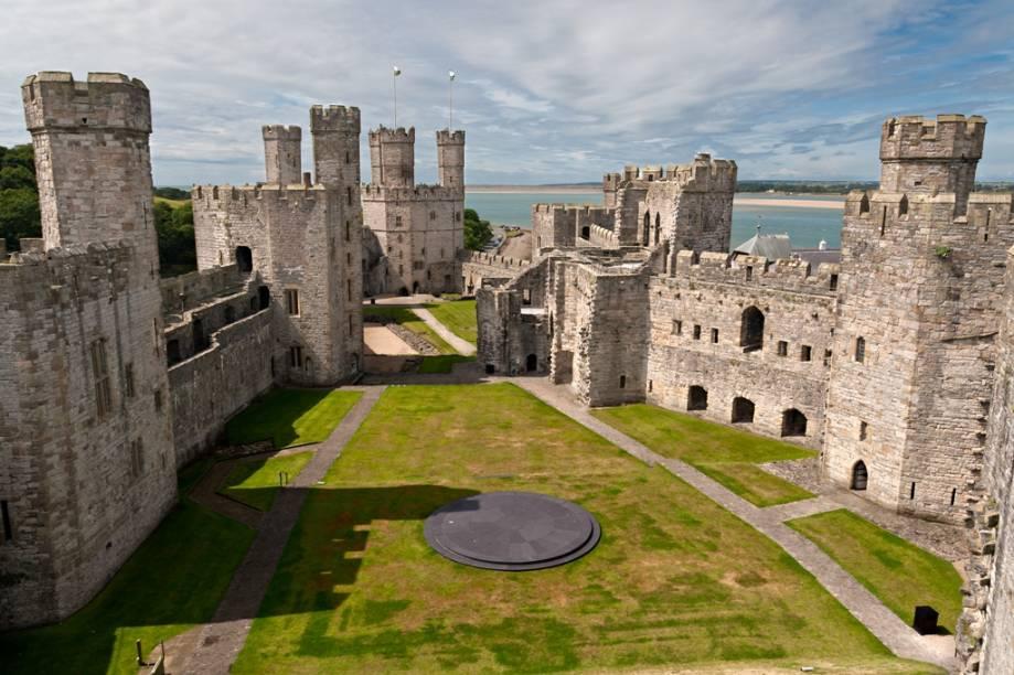 <strong>Castelos do País de Gales:</strong> O rei Eduardo I, Longshanks, não entrou para a história por sua graça e simpatia. Durante boa parte da segunda metade do século 13 ele imprimiu uma feroz política expansionista sobre os vizinhos <strong>Escócia</strong> e <strong>País de Gales</strong> que até hoje são combustível para ferozes conversas de pub. Assim que definia seu domínio sobre suas novas conquistas, assegurava-as construindo fortalezas tão inexpugnáveis como majestosas. Com uma arquitetura bélica primorosa, ele queria mostrar quem era o novo senhor do pedaço. A linha defensiva formada pelos castelos de Caernarfon (foto), Conwy, Harlech e Beaumaris, à sombra do <strong>Parque Nacional de Snowdonia</strong>, é listada em conjunto como Patrimônio da Humanidade pela Unesco e marco definitivo deste período. Curiosidade: o título de Príncipe de Gales, tal como o conhecemos hoje (o de príncipe-herdeiro do trono inglês), foi inaugurado pelo filho de Longshanks, o fraco Eduardo II. <strong>Distância de Londres: 450 quilômetros</strong>