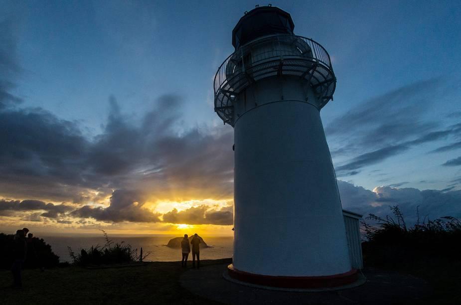 Turistas observam o pôr do sol a partir do farol de Gisborne