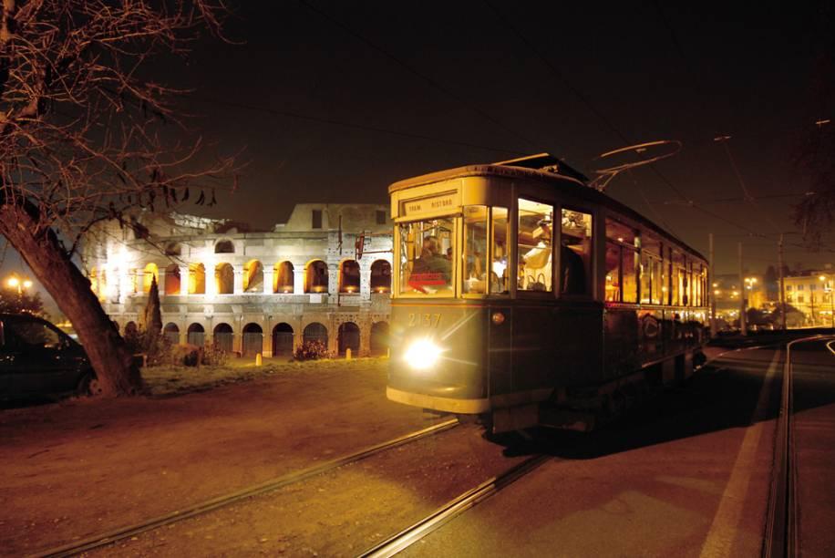 Vista noturna de bonde com o Coliseu Romano ao fundo