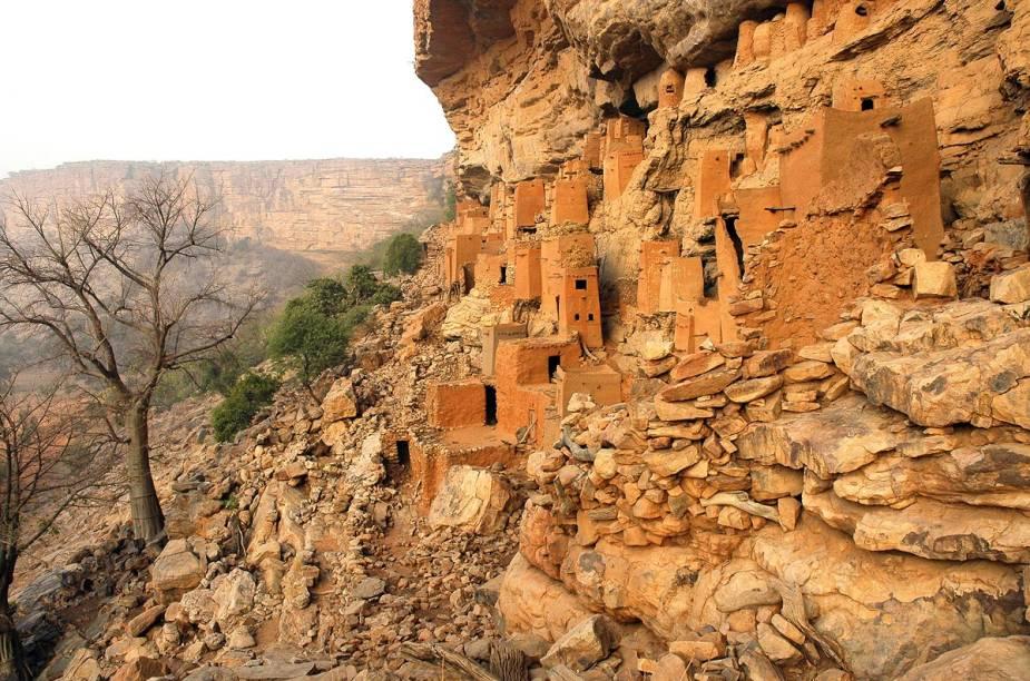 """<strong>Pays Dogon (Mali)</strong>        A trilha que percorre a região """"do povo Dogon"""", conhecido por seus dançarinos mascarados, pode durar até 10 dias e leva aos penhascos da falésia de Bandiagara, que servia de refúgio natural para os dogons. Lá, eles construíam casas feitas de argila, palha e esterco bovino, quase imperceptíveis à distância e acessíveis apenas escalando as rochas"""