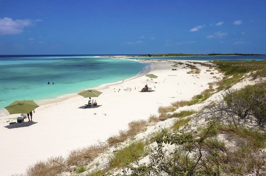 """<strong><a href=""""http://viajeaqui.abril.com.br/cidades/venezuela-los-roques"""" rel=""""Los Roques (Venezuela)"""" target=""""_blank"""">Los Roques (Venezuela)</a></strong>O arquipélago venezuelano de Los Roques tem atraído muitos visitantes brasileiros nos últimos anos – e não é difícil encontrar o porquê: poucos lugares da América do Sul tem praias de águas tão cristalinas em ambientes tão isolados como as ilhas da República Boliviariana. São, ao todo, 47 ilhas e 250 bancos de areia espalhados pelo mar do Caribe, pelos quais se espalham nada mais que 1.200 habitantes (muitos deles europeus, donos da maioria dos pousadas e hotéis do balneário)."""