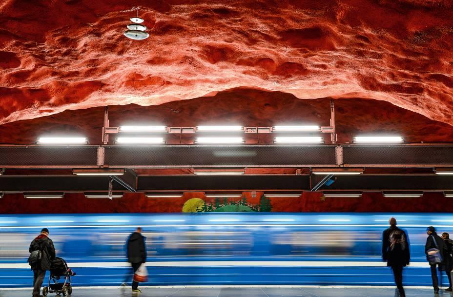 """<strong>Que viagem!</strong>Isso é que é democratização das artes plásticas. Mais de 90 das 100 estações de metrô de <a href=""""http://viajeaqui.abril.com.br/cidades/suecia-estocolmo"""" rel=""""Estocolmo"""" target=""""_blank"""">Estocolmo</a> são decoradas com esculturas, mosaicos, pinturas, instalações, gravuras e relevos feitos por 150 artistas. É a maior exposição de arte do mundo, com 110 quilômetros de extensão. São coisas espantosas como a estação Solna, aqui na foto. Os passageiros esperam o metrozinho de cada dia admirando uma caverna vermelha e verde com pinturas que mostram temas candentes na <a href=""""http://viajeaqui.abril.com.br/paises/suecia"""" rel=""""Suécia"""" target=""""_blank"""">Suécia</a> dos anos 70, do despovoamento rural ao ambientalismo. A obra é dos artistas Anders Aberg e Karl-Olov Bjor"""