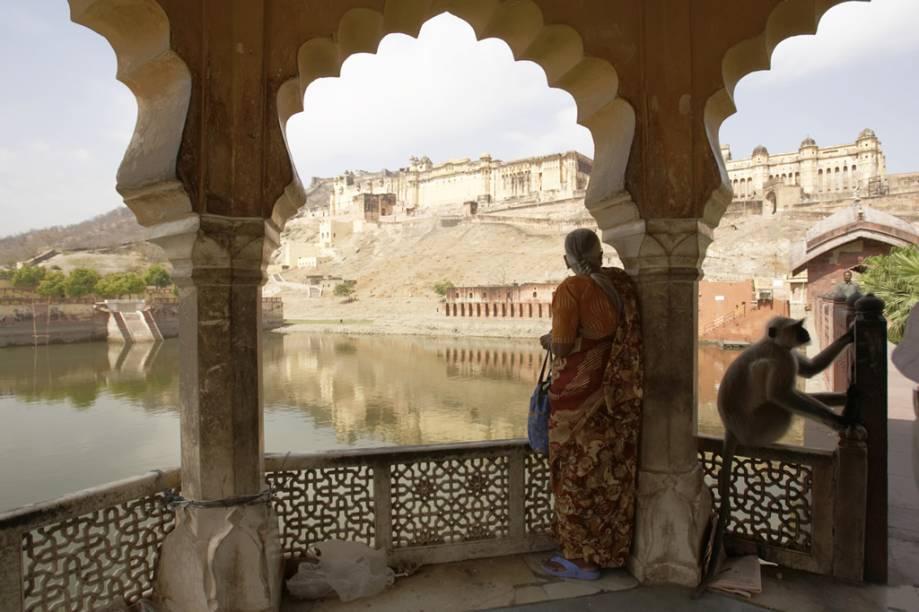 Mulher avista ao longe as poderosas muralhas do Forte Amber, em Jaipur, na Índia