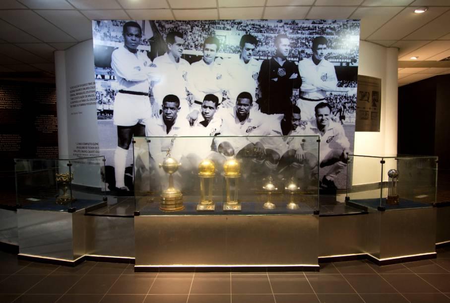 As taças dos títulos mundiais do Santos e, ao fundo, a foto do time campeão