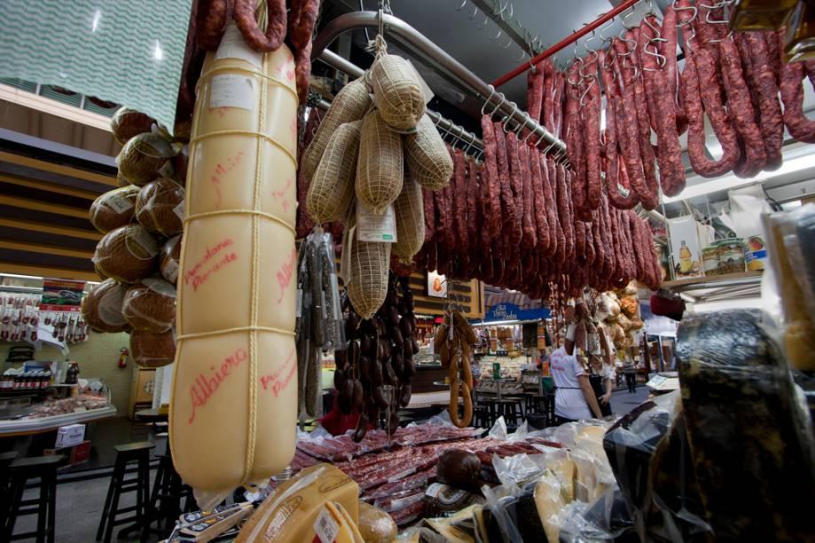 As linguiças artesanais e queijos gigantes, como este provolone com mais de um metro de altura da Galeria do Bacalhau, também estão entre as delícias vendidas nas lojas do Mercadão