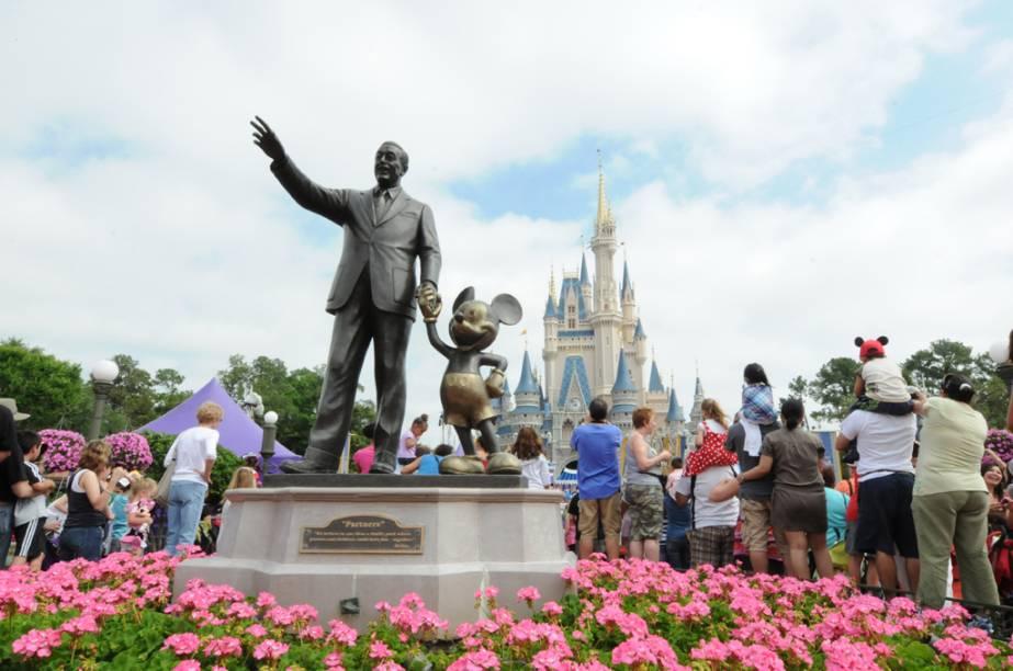 Estátua de Walt Disney com o Mickey Mouse e o Castelo da Cinderela, ao fundo, no parque temático Magic Kingdom