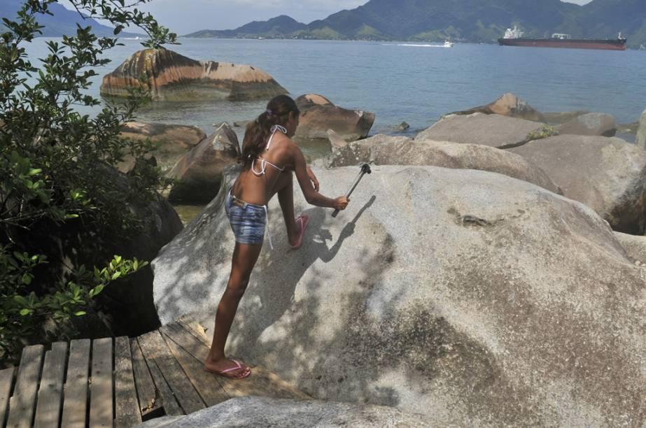 Turista bate o martelo para ouvir o som oco da <strong>Pedra do Sino</strong>, na Praia Garapocaia (ou Praia da Pedra do Sino)