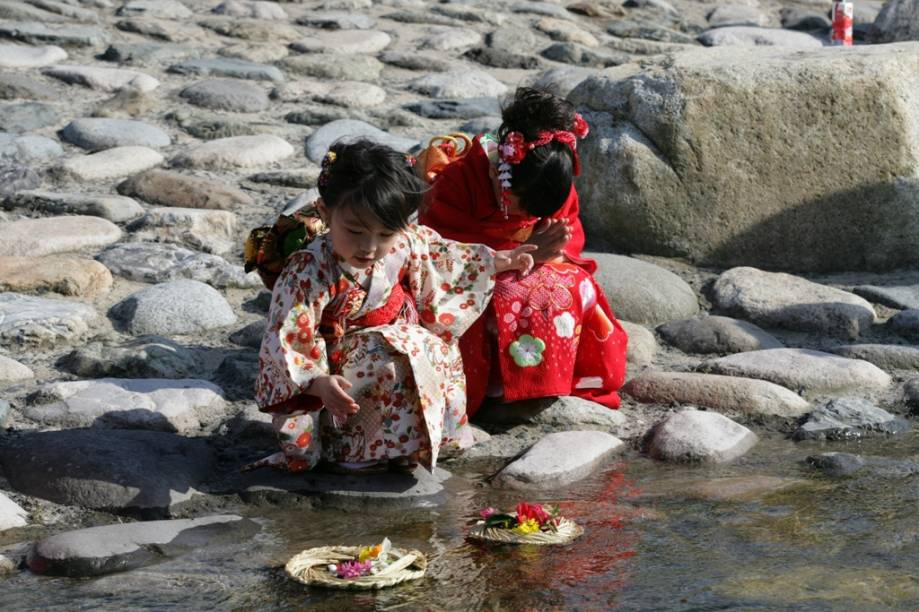 Meninas enviam para o mar um barquinho de palha com treze bonequinhos de papel, num ritual chamado nagashibina, realizado no dia das meninas. Tottori, centro-leste do Japão