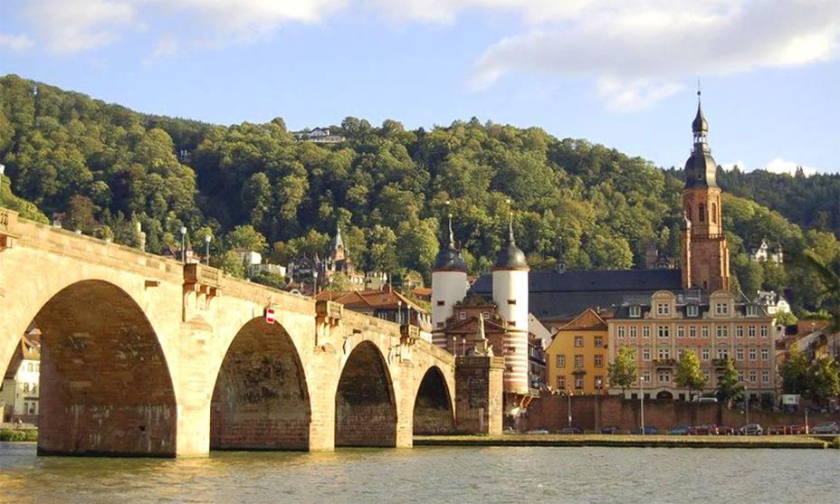 """Localizada no <strong>Vale do Rio Neckar</strong>, <strong>Heidelberg</strong> é considerada como uma das cidades mais românticas do país graças ao seu castelo imponente, com mais de 700 anos, e à beleza da <strong>Ponte Alter Brücke</strong>. Fontes, praças, mansões, cafés e lojinhas completam a atmosfera delicada do local, que, em contraponto aos apaixonados que procuram a região, também concentra uma boa quantidade de estudantes graças às suas universidades.<a href=""""http://www.booking.com/city/de/heidelberg.pt-br.html?aid=332455&label=viagemabril-vilasalemanha"""" target=""""_blank"""" rel=""""noopener""""><em>Busque hospedagens em Heidelberg no Booking.com</em></a>"""