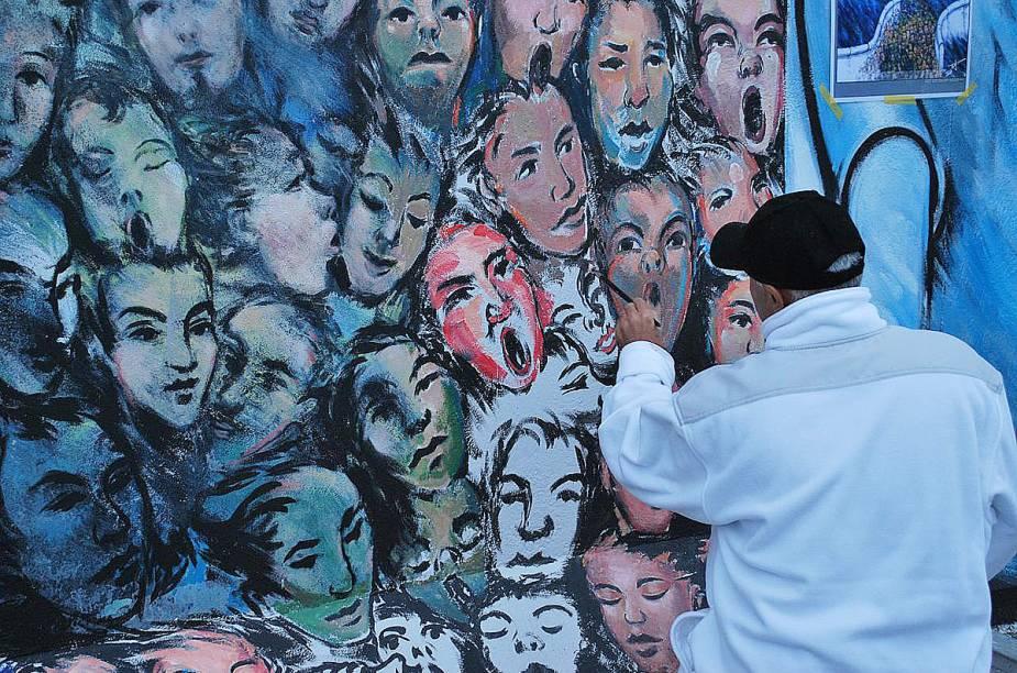 Artista retocando sua obra no muro