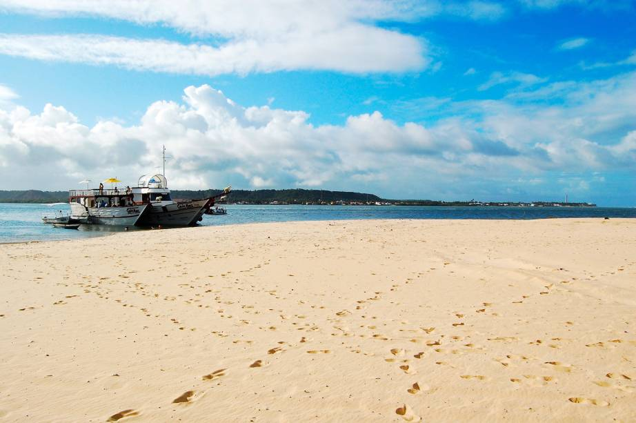 Em um canto da praia estão barracas com serviço de praia e em outro pouco movimento com falésias coloridas