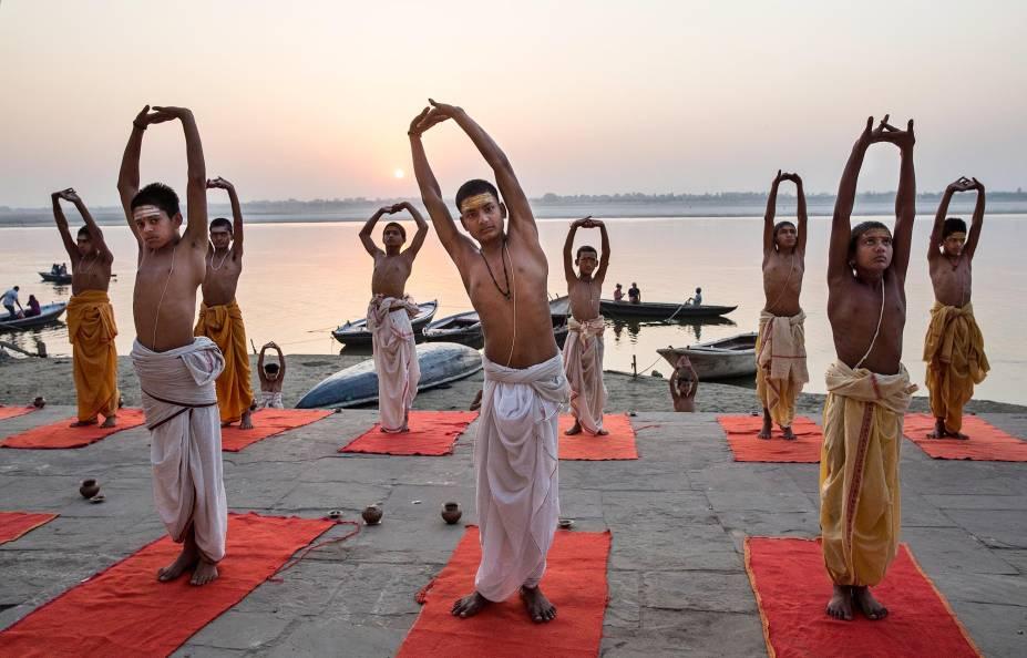 Jovens hindus praticam ioga na beira do rio Ganges, em Varanasi
