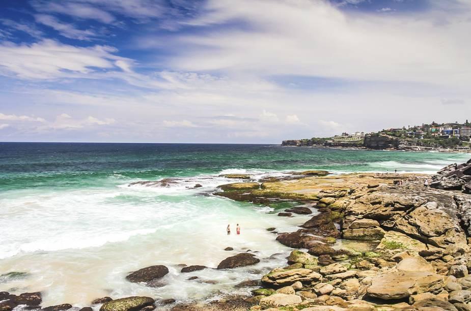 """<strong><a href=""""http://viajeaqui.abril.com.br/cidades/australia-sydney"""" rel=""""Sydney (Austrália)"""" target=""""_blank"""">Sydney (Austrália)</a></strong>                                        Outras praias que valem muito uma visita em um dia de sol são Manly, Bronte (é a praia da foto, acessível através de uma trilha que começa em Bondi Beach), Collaroy e Palm Beach. Após se bronzear nas orlas, o turista ainda pode desfrutar de diversos outros atrativos do centro de Sydney, como a fantástica Opera House e a imponente Sydney Bridge, que pode ser escalada pelos mais aventureiros."""