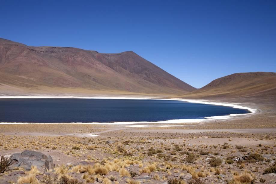 O contraste entre as cores da areia, a rala vegetação, as águas verdes das lagoas Meñiques e Miscanti e os picos nevados ao fundo são um convite à meditação