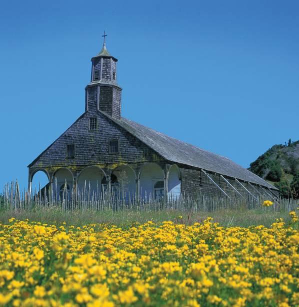 """A <strong>Ilha de Chiloé</strong>, a 90 quilômetros de <a href=""""http://viajeaqui.abril.com.br/cidades/chile-lagos-andinos"""" rel=""""Puerto Montt"""" target=""""_blank""""><strong>Puerto Montt</strong></a>, reúne um conjunto arquitetônico do século 19, com casas sobre palafitas e mais de 60 igrejas de madeira. Destas, 16 são consideradas Patrimônio da Humanidade pela Unesco"""