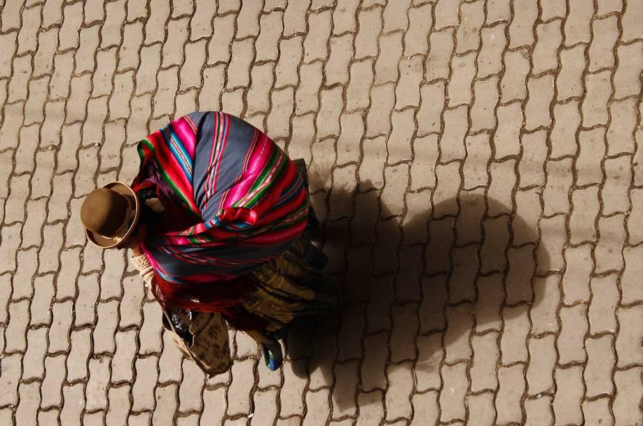 Mulher indígena de La Paz caminha com sua típica trouxa colorida pelas ruas do centro da capital boliviana