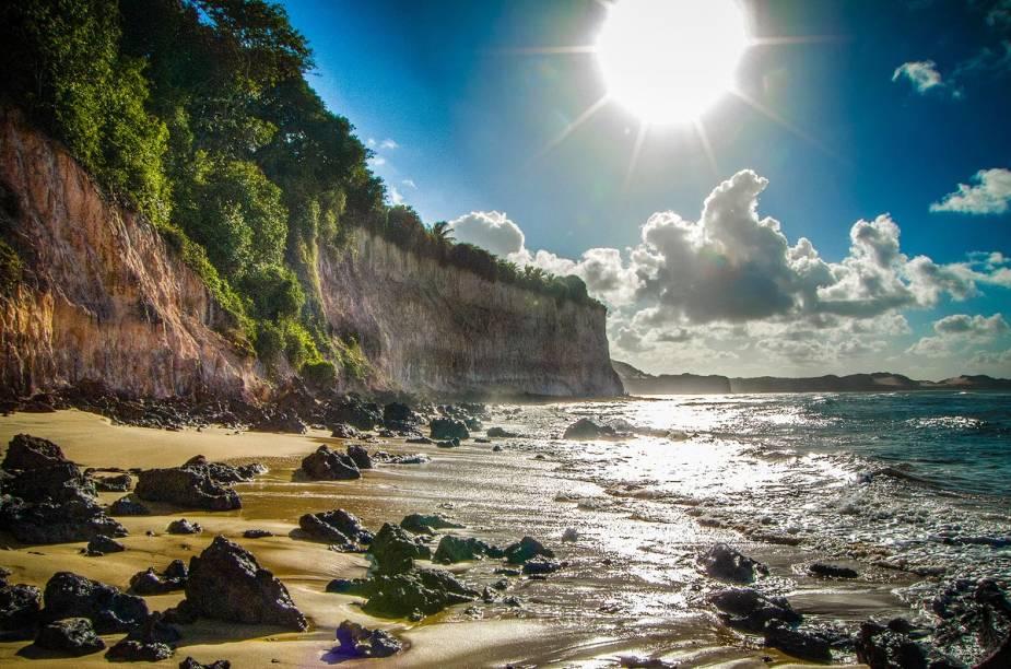 Na maré alta, a faixa de areia quase some entre o mar e as falésias