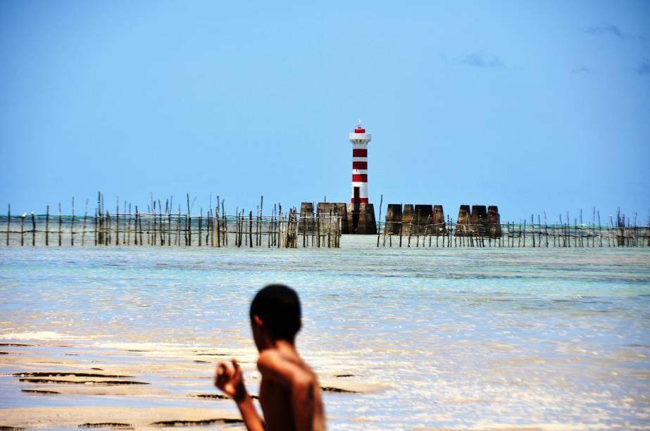 Garoto corre em frente ao farol da praia de Ponta Verde, em Maceió (AL)